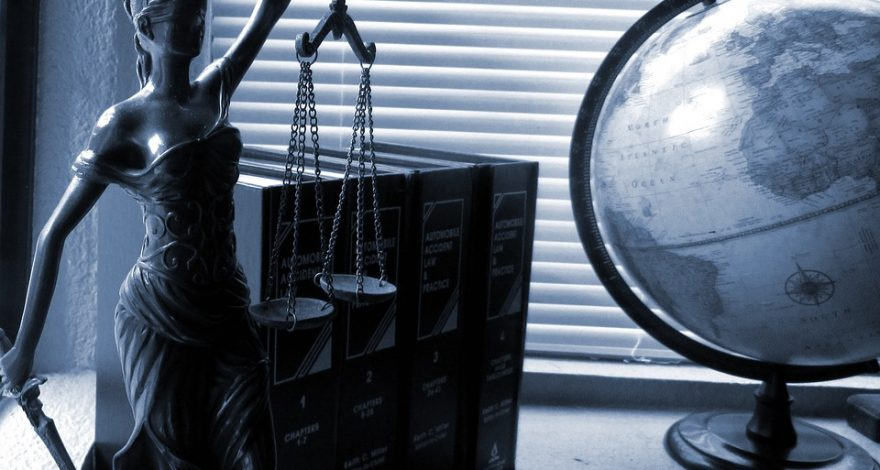Scales of justice on a desk with law books and a globe