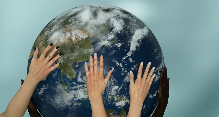 multiple hands holding up a globe in support of cross-border communication