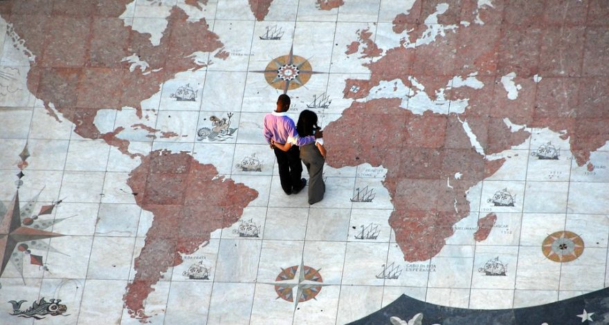 couple standing on a large world map