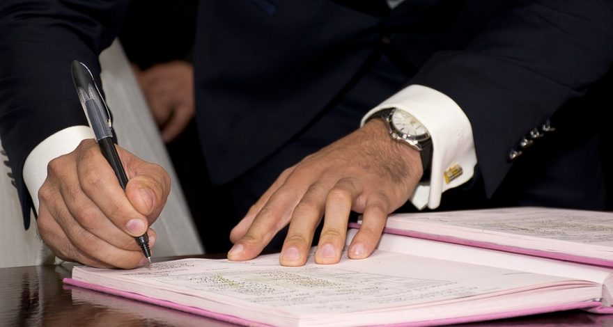 man signing a prenuptial agreement