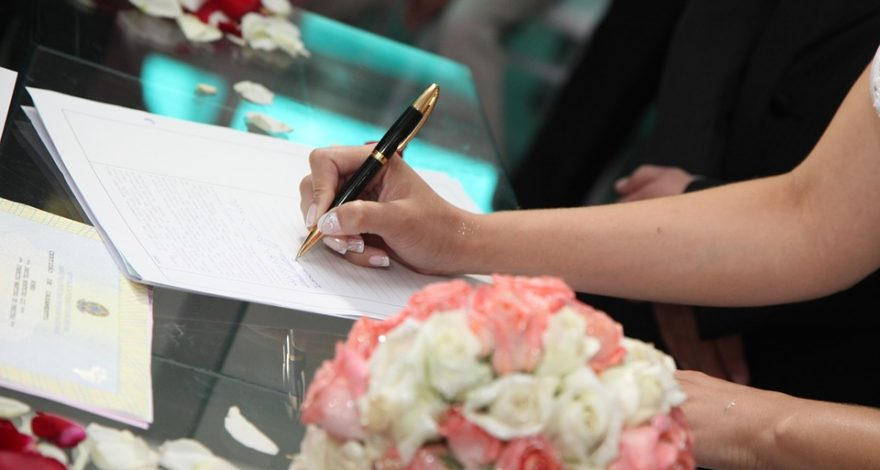 bride signing marriage certificate that requires translation services