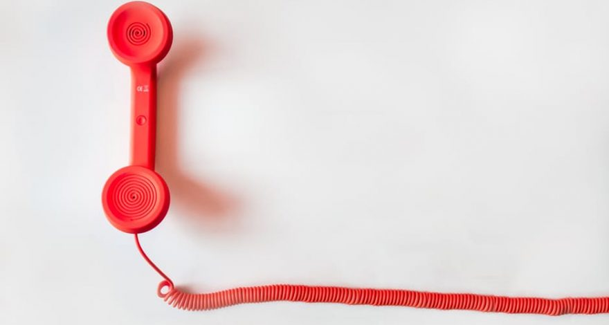 red telephone and cord demonstrating telephonic interpreting during emergencies