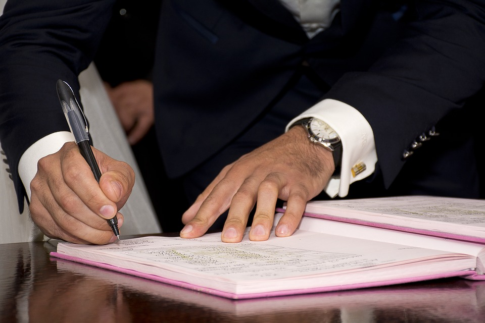 man signing a translated affidavit
