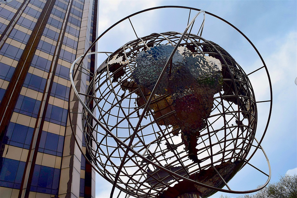 metal globe against skyscrapers - language services