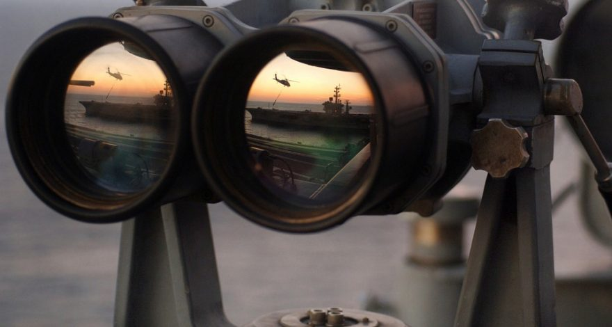 binoculars being used to spy on a rival country's naval force