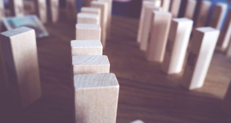 wooden blocks set up like dominos